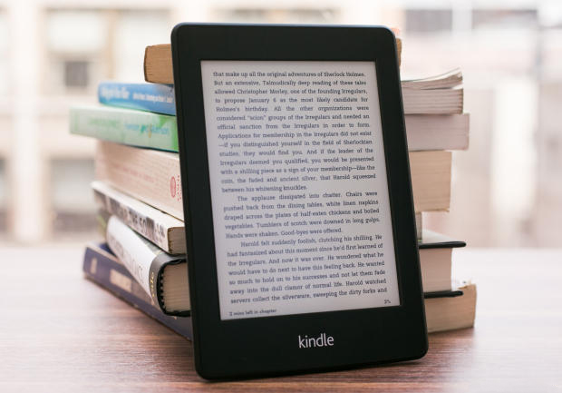 A Kindle ereader leant against paperbacks